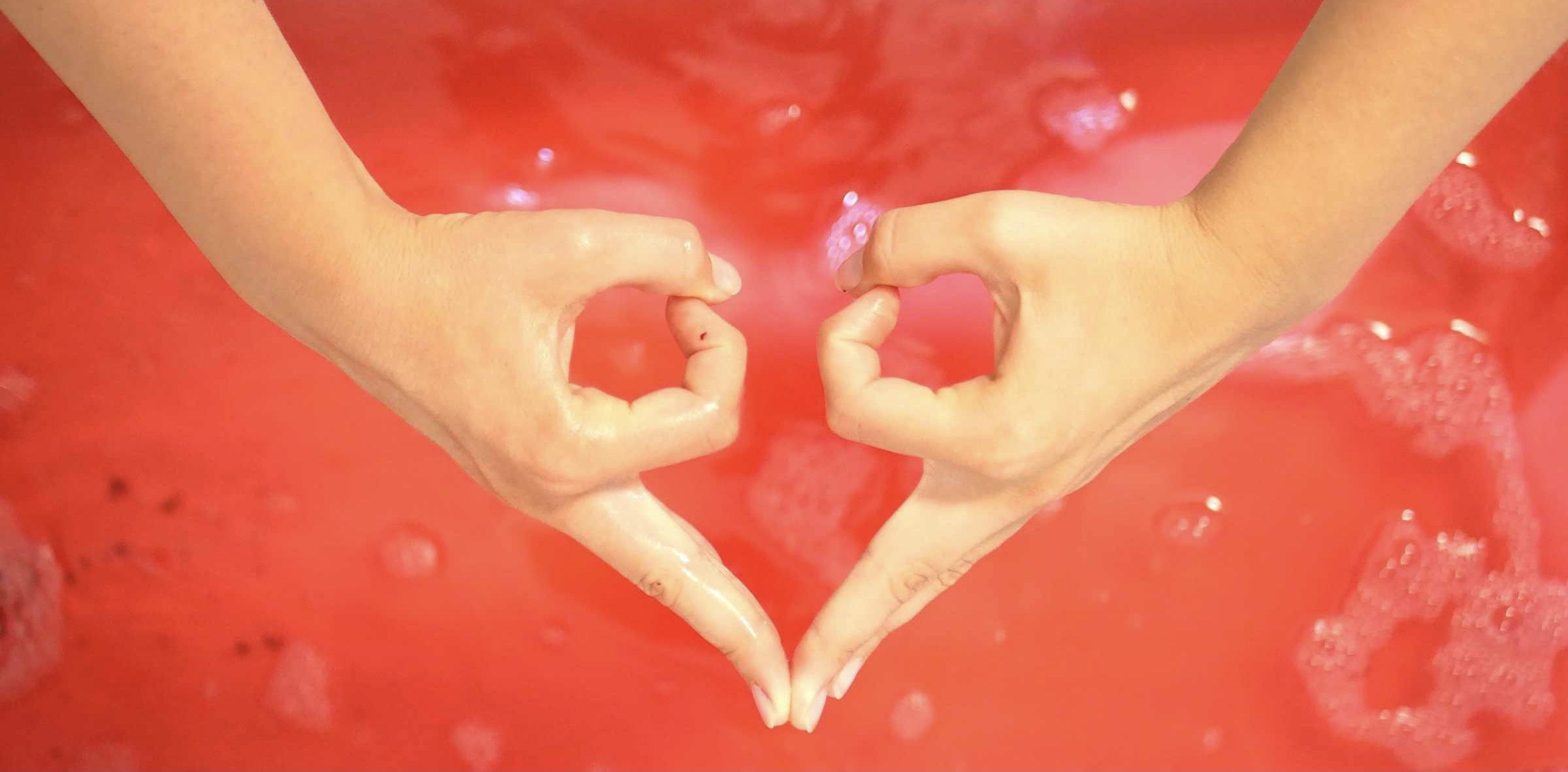 Zwei Hände, die mit den Fingern die Form der Eierstöcke nachahmen, vor rotem Hintergrund
